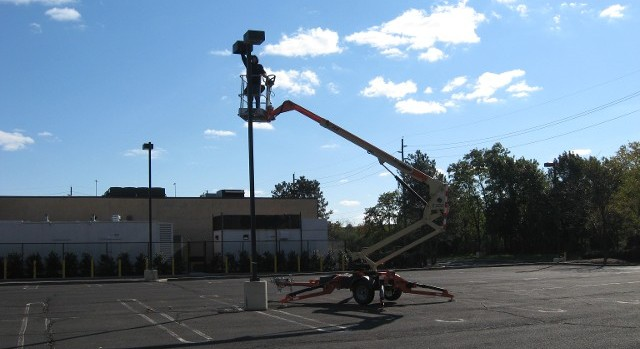 Man Doing Electrical Work In a Parking Lot